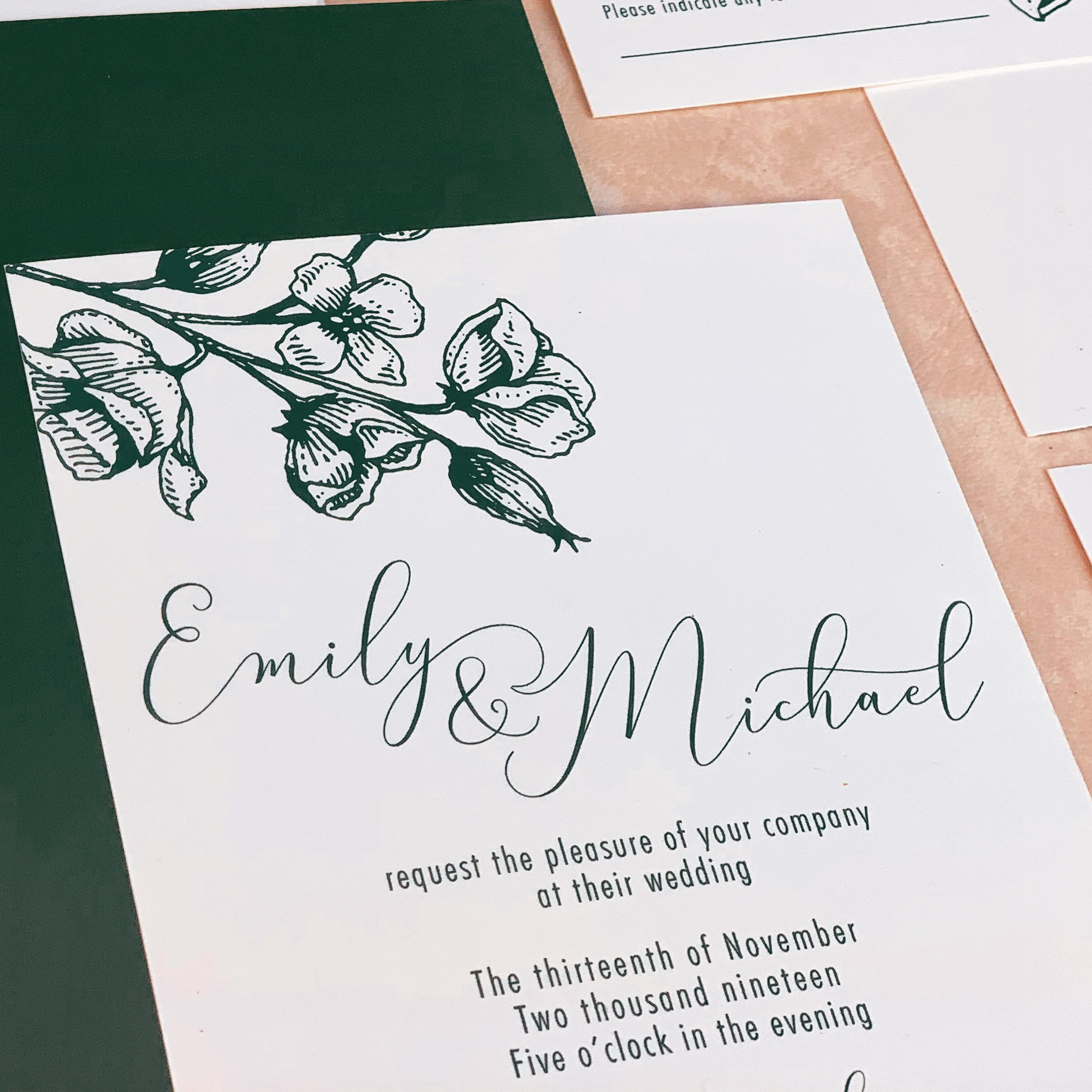 Invitation with floral design and sample bride and groom named Emily and Michael